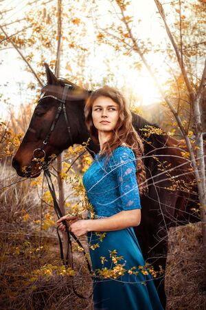 Beautiful girl in a blue dress looks into the distance. A brown horse is standing nearby. Fairytale photography, artistic. Girl and horse in the forest. Banco de Imagens