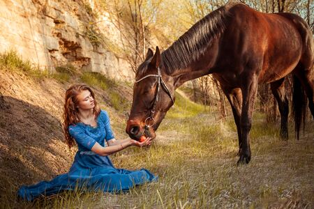 Beautiful girl in a blue dress feeds a horse with an apple from her hands. Fairytale photography, artistic, magical. Girl and horse in the sunset light. Love for horses.