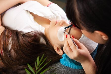 Master increases eyelashes of a young girl in a beauty salon. Professional eyelash extensions. Green tropical flower in the interior.