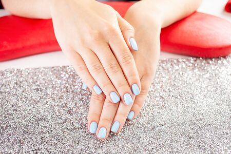 Das Endergebnis der Maniküre. Schöne blaue Nägel. Der Prozess der Maniküre in einem Schönheitssalon. Salon in schwarz, rot, weiß.