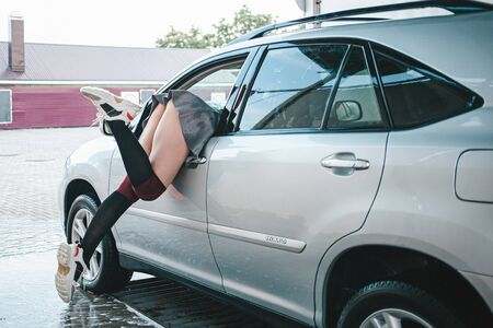 Beautiful pumped-up girl sticks out of the car. The girl pulls things out of the car through the window. Sexy woman in a car wash. Standard-Bild