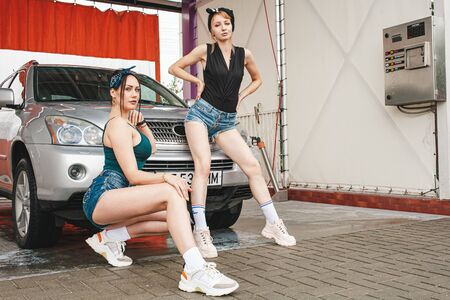 Two hot girls in frank clothes pose next to expensive cars. Professional models in the washing of cars in the open air. 版權商用圖片