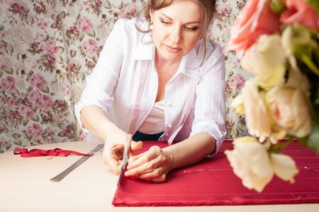 A seamstress woman cuts off the excess red fabric, the girl in the atelier cuts out the details of the pattern for future clothes. The master makes clothes with his own hands. Small business
