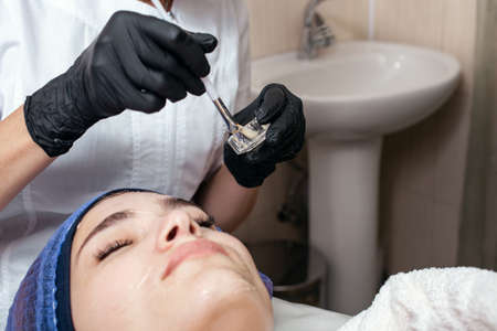 The beautician massages the face in the beauty salon. Improves blood flow, lymph outflow, increases skin elasticity, tones muscles, improves complexion, smooths wrinkles, reduces puffiness. Standard-Bild