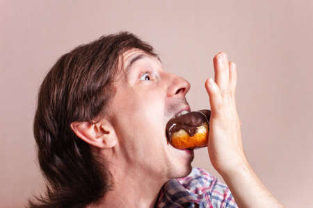 A man chooses between white and black chocolate. Funny man looks at the chocolate donut, a very funny photo on a white background. Empty space for text. A man loves sweets chocolate.