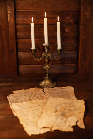 Magical writings, piles, aged paper, candles, wooden brown background Halloween celebration