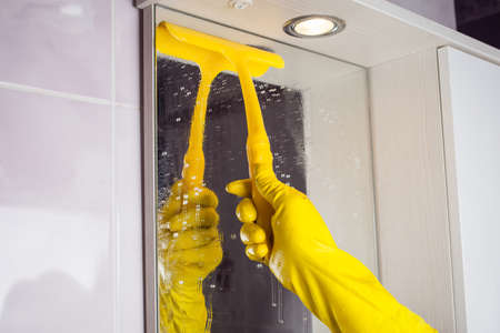 Maid with rubber glove cleaning tap and sink. Housekeeping scrubbing and polishing silver tap in bathroom. Stock fotó