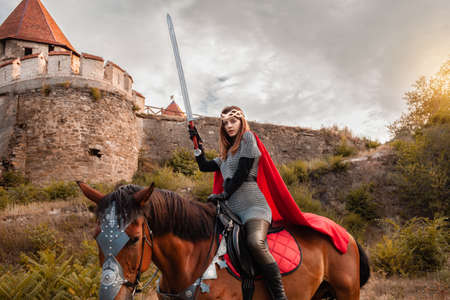 A beautiful girl with a sword in a medieval fantasy suit. A woman in a chain mail, crown, on a horse in combat ammunition. A girl riding a horse against the backdrop of the fortress.