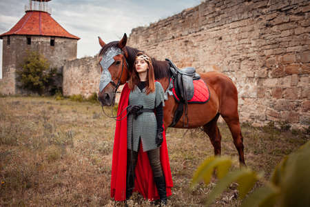 A beautiful girl stands next to a horse against the background of a medieval fortress. Fantasy costume, chain mail, cloak. A woman in a magic costume of the warrior queen.