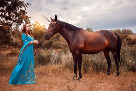 Beautiful young female elf with long dark wavy hair petting her horse resting in the woods forest. nymph stroking her horse care pet love animals harmony caring owner gentle. Stock Photo