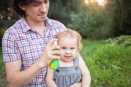 Dad treats his daughter with mosquito spray. The man uses spray on the child's arms and legs. Protection from mosquitoes in the forest. Spray from mosquitoes in nature and recreation.