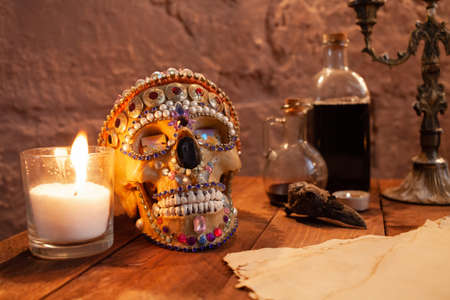 Photo zone in the studio for Halloween. Dramatic scenery for All Saints Day celebrations. The skull is decorated with beads and stones, candles, ink, crows skull, old parchment on atable.