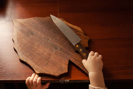 The child pulls a knife from the table, danger. The child can cut, children's home dangers. A little one-year-old girl with a knife.