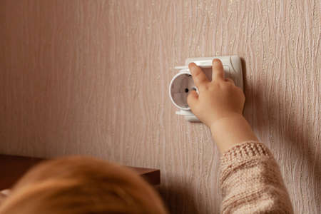 The child plays with an outlet, pulls his hands to it, sticks his fingers. The child is in danger at home. Baby fingers in the socket. Fear Stock fotó