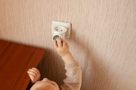 The child plays with an outlet, pulls his hands to it, sticks his fingers. The child is in danger at home. Baby fingers in the socket. Fear