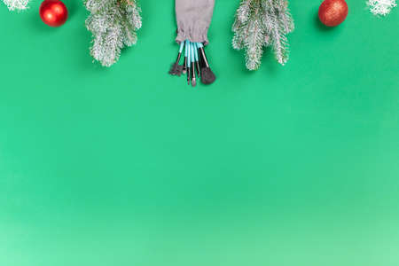 Christmas, New Year's background for make-up artist. Make-up brushes, Christmas decorations, spruce. Empty space for text. 写真素材