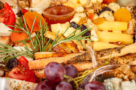 A box of food, cheese, breads, fish, shrimp. Food delivery for the company, romantic, office dinner at home. Beautiful composition of food in a box, convenient carrying, fresh products.