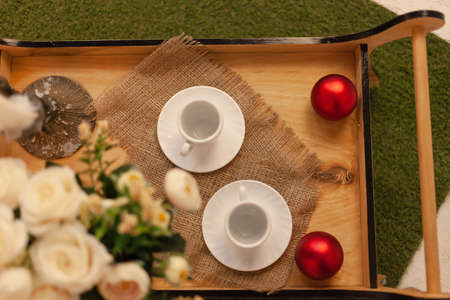 A tray with two cups of coffee. A bouquet of roses, Christmas toys. Christmas photo zone, beautiful entourage for breakfast.