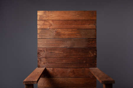 A wooden throne chair on a gray background in a photo studio.