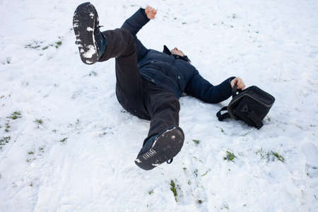 A man falls in the snow. The man slipped and was injured. Falling on slippery ice. Winter. Fracture, bruise, dislocation.