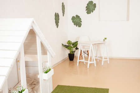White beige interior, table and fashionable chair. Green plants are monstera flowers. Workplace, bedroom. Decorations for the interior with own hands, empty space for text.