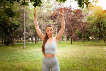 A beautiful young woman performs exercises in the park, on the grass, outdoor. Yoga, fitness, muscular trained body. Sunny glare. A healthy lifestyle. Workout, forest in the city. Park recreation area Standard-Bild