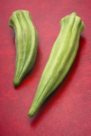 Fresh okra (Abelmoschus esculentus) on red background photo