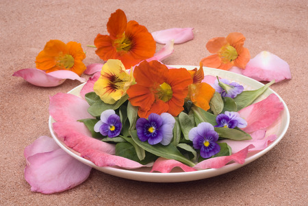 salad of edible flowers in ceramic dish. colorful summer dish. with nasturtiums, pansies, roses and mache. photo