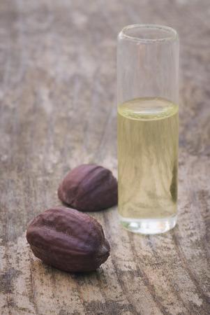 Jojoba (Simmondsia chinensis) seeds and oil on wooden table Archivio Fotografico