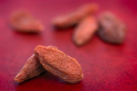 barbarum: dry red goji berries (Lycium barbarum) on red background Stock Photo
