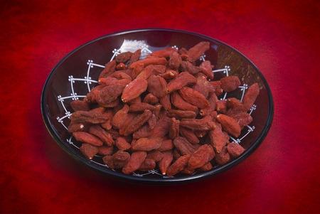 lycium: dry red goji berries (Lycium barbarum) on red background Stock Photo