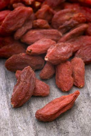 lycium: dry red goji berries (Lycium barbarum) on wooden table Stock Photo