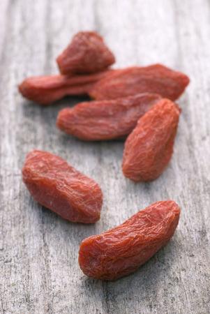 barbarum: dry red goji berries (Lycium barbarum) on wooden table Stock Photo