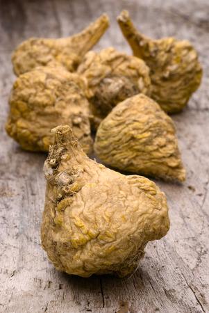 maca root: Peruvian ginseng or maca (Lepidium meyenii), dried root on wooden table Stock Photo