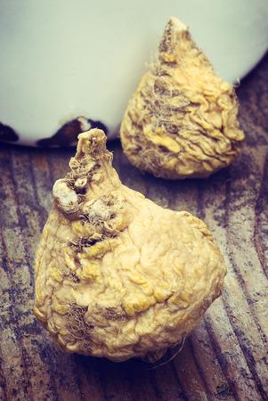 maca: Peruvian ginseng or maca (Lepidium meyenii), dried root on wooden table Stock Photo