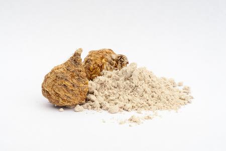 maca: Peruvian ginseng or maca (Lepidium meyenii), dried root and  powder on wooden table