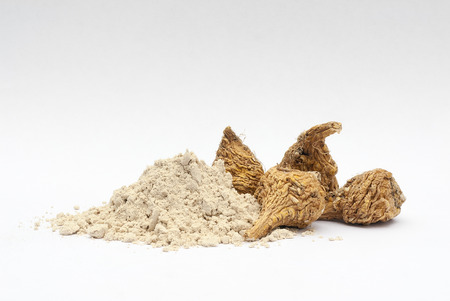 aphrodisiac: Peruvian ginseng or maca (Lepidium meyenii), dried root and  powder on wooden table