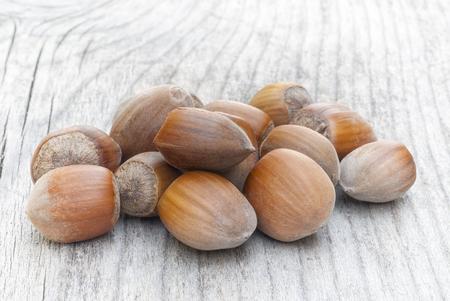 Hazelnuts on wooden table, fruit of hazel (Corylus avellana), tree native of Europe.
