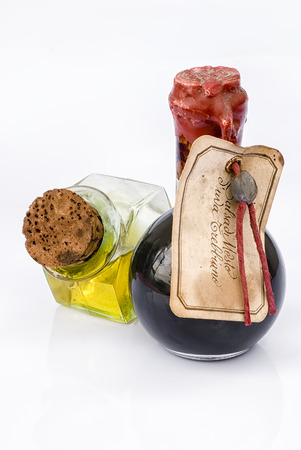 Traditional Balsamic Vinegar and pouring virgin olive oil on a white background, products of Italian excellence