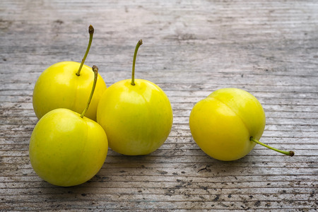 yellow Cherry plum (Prunus cerasifera). ripe of fruit on woody table