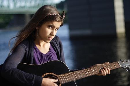 Ritratto di ragazza con una chitarra vicino al fiume