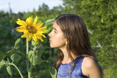 Girl smelling sunflower in garden photo