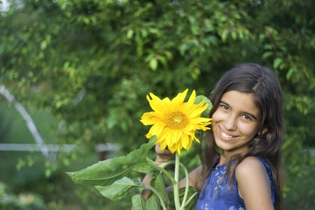 Girl with sunflower in garden photo