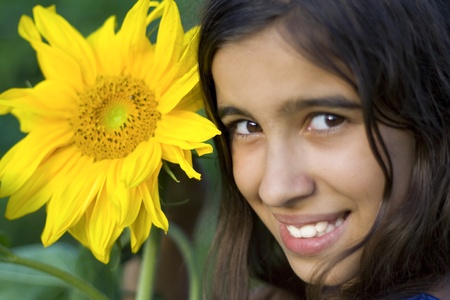 Close up portrait of brunette girl with sunflower