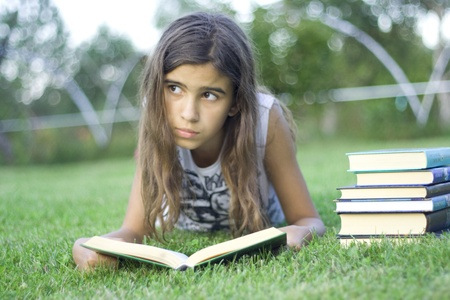Girl reading a book on the grass
