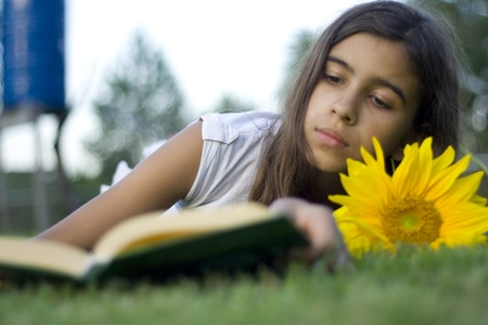 Ragazza la lettura di un libro in giardino