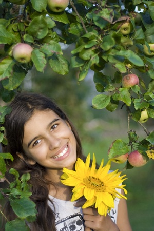 Girl with sunflower in autumn garden Stock Photo