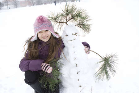 Happy girl with her snowman Stock Photo