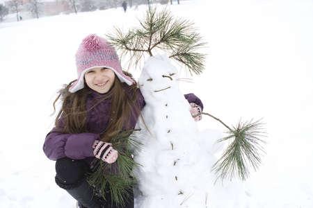 Ragazza felice con il suo pupazzo di neve Archivio Fotografico