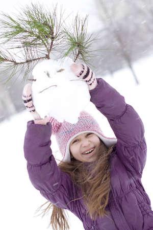 Ragazza felice rendendo pupazzo di neve Archivio Fotografico